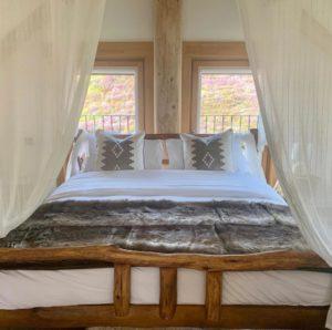 Спальня из дерева в доме со сруба